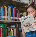 Una bambina legge un libro che le insegna a rispettare i suoi amici
